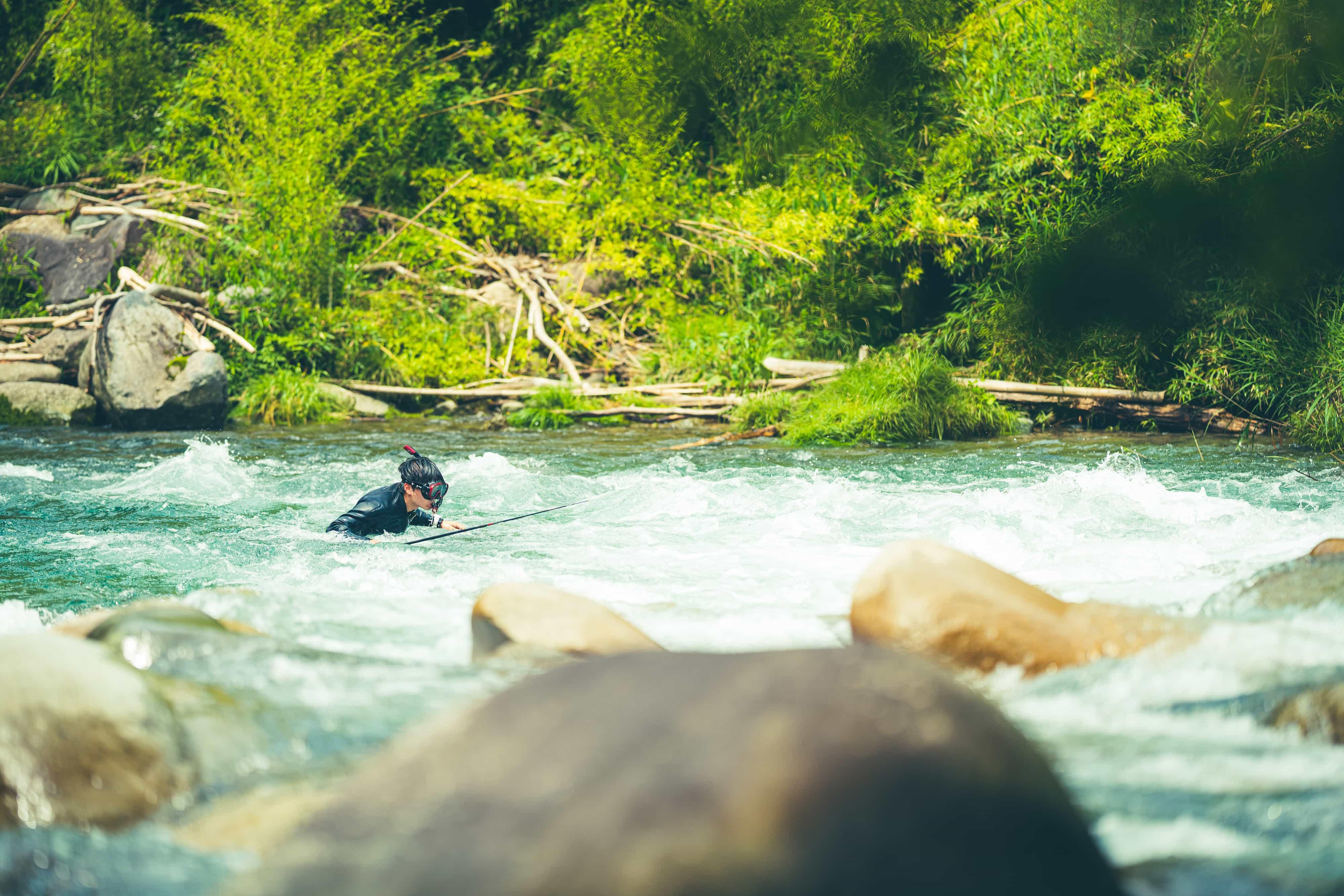 川を泳いでいる男性